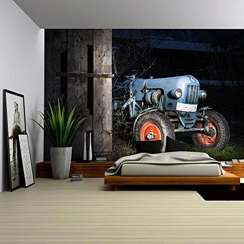 wall26 - Blue Oldtimer Farming Tractor Standing Next to a Wooden Hut at Night with Red Painted Tires - Removable Wall Mural | Self-adhesive Large Wallpaper - 66x96 inches