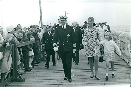 Vintage photo of Albert II of Belgium and Queen Paola of Belgium walking with their child and several people gathered to see them.