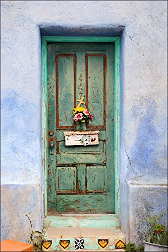 Colorful American Southwest painted green door with flowers mailbox and cross on adobe blue wall.