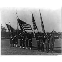 Photograph: A view of Marine, Bluejacket, and WAVE color guards on Ross Field Photograph shows twelve color guard representatives, four women for WAVE, four men for Bluejacket, and four men for the Marines, standing at attention holding flags. A view of Marine, Bluejacket, and WAVE color guards during a military review on Ross Field at the U.S. Naval Training Center, Great Lakes, Illinois between ca. 1943 and ca. 1948