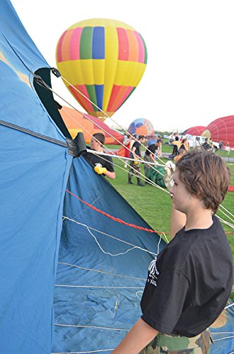 Raily Blankley, a member of the New Mexico Civil Air Patrol, holds the balloon opening as it is infl