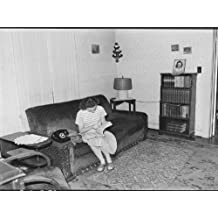 """Photography Poster - Daughter of Cecil Allgood, miner, looks up a number in the telephone directory. Her home is part of company housing. 9"""" x 13"""""""