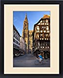 Framed Print of Bicycler rides past the massive Cathedral Notre Dame in Strasbourg, Bas Rhin