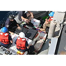 LAMINATED POSTER Coast Guard Law Enforcement Detachment and Navy crew members plan the transfer of several bales of i