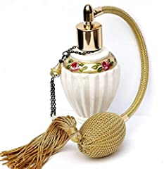 An elegant white glass vanity bottle featuring fluted edges, antiqued gold detailing, and hand-painted pink roses! A vintage-style bulb sprayer adds a touch of elegance and a handmade tassel, created with a golden crystal glass bead and tiny ...