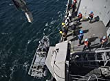 A knuckle-boom crane lowers a rigid hull inflatable boat aboard USS Mesa Verde (LPD 19) into the Atl