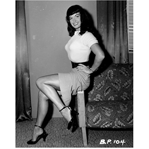 Back Movie Photo (Bettie Page Seated on Arm of Chair Kicking Heal Back Smiling 8 x 10 Inch Photo)