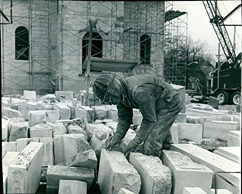 Vintage photo of A workman checks the numbered stones that still have to be stored.
