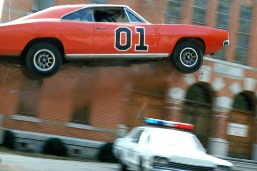 Dukes Of Hazzard General Lee flies in air over Plymouth Fury police car 24X36 Poster