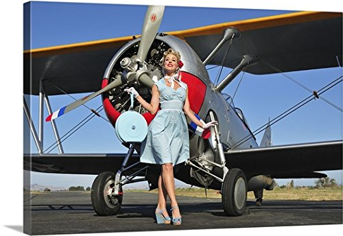 Christian Kieffer Gallery-Wrapped Canvas entitled Elegant 1940's style pin-up girl standing in front of an F3F biplane by greatBIGcanvas