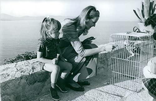 Vintage photo de Eva Renzi alimentación un pájaro en una jaula ...