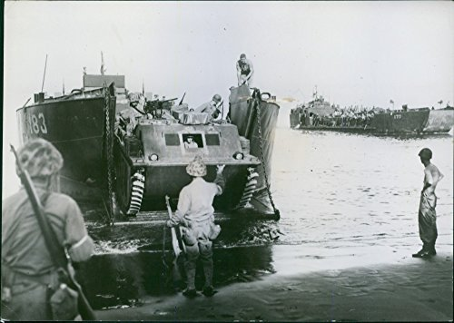 (Vintage photo of An American amphibious armored vehicle starts down the lowered ramp of an LCT vessel to the beach at Cape Gloucester, new Britain Island, during landing operations there by U.S. Marines.)