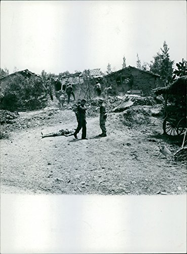 Destroyed House (Vintage photo of Two soldiers having a conversation beside a man laying on the ground, while the other soldiers are looking through the rubble of a destroyed house.)