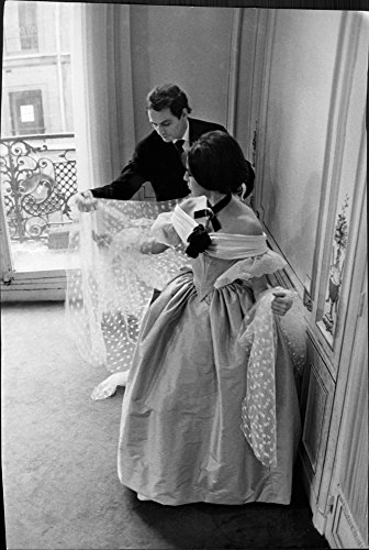 (Vintage photo of Pierre Cardin helping to wear cloth.)
