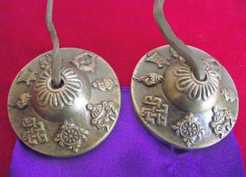 Tibetan Buddhist Astamangala Hand Bells on Leather Cord; embossed with the 8 Buddhist Symbols of Happiness - 60mm Diameter; comes in a Satin Drawstring Pouch. Use as a Meditation Aid; for Space Clearing; Healing - Sold by Spiritual Gifts. Usually dispatched within 2 working days.