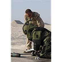 A member of Navy Explosive Ordnance Disposal Mobile Unit assists another team member in rendering safe an Improvised Explosive Device (IED). Poster Print (11 x 17)