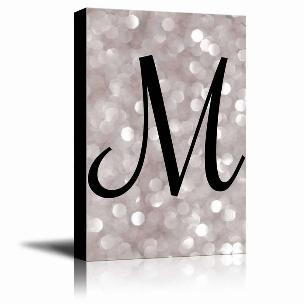 the letter m in brush stroke cursive on a champagne colored bokeh