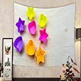 Madeleine Ellis Custom tapestry silicone molds with starry and love shapes of different colors on a wooden surface concept of