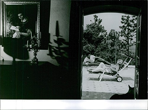 Vintage photo of Portrait of a French singer from Cairo, Egypt Richard Anthony siting outside the house and talking to his wife. 1964