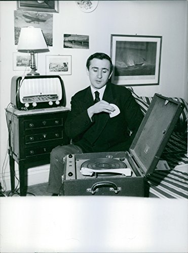 (Vintage photo of A man alone in his room sitting in his bed and listening to his turntable playing)
