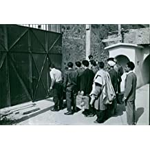 Vintage photo of People standing in front of the gate, with police watching them, during the war in Algeria.