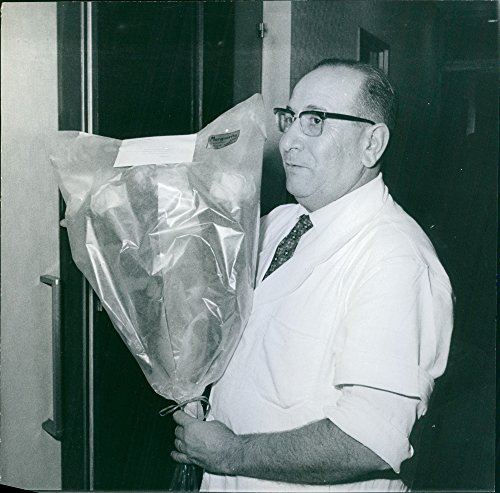 Vintage photo of A photo of a man holding a bouquet of flowers for Marguerite, 1964.