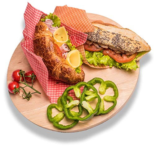 Sandwiches in beeswax wraps beside cut green bell peppers and tomatoes on wood chopping board.