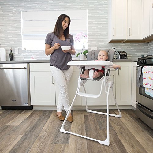 A mother stands with a bowl on hand while her baby sits on a folding high chair.