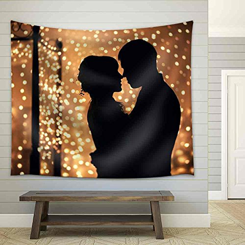 Hugs Lovers in Silhouette Against The Background of Garlands of Lights Fabric Wall