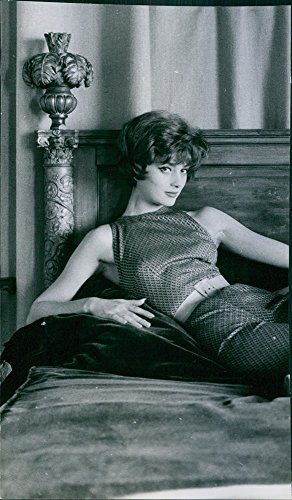 Vintage photo of A beautiful Marie Helene Arnaud is lying on a bed during her modeling career.