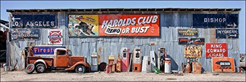 Fine art panoramic photograph of an old truck and vintage gas station items along with an airplane hangar with many California desert ghost signs attached. Panoramic photo perfect for man cave.