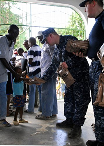 Home Comforts Laminated Poster A Haitian boy receives a (MRE) from Sailors assigned to The Dock-Landing Ship USS Carter Hall (LSD Vivid Imagery Poster Print 24 x 36