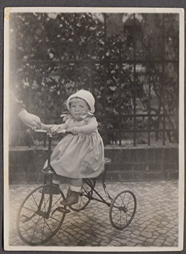 Little girl in knit bonnet on tricycle with bell snapshot ca 1920s