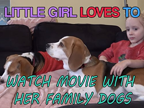 Little girl loves to watch movie with her family dogs