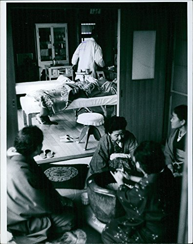Vintage photo of Doctor treating the patient with people sitting outside the room in Japan, 1961. (1961 Japan)