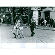 Vintage photo of A police chasing off the woman with two boys, crying, while crossing the street, during the war in Algeria.
