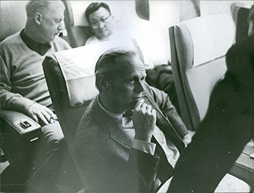 Vintage photo of Richard Widmark aboard an airplane.