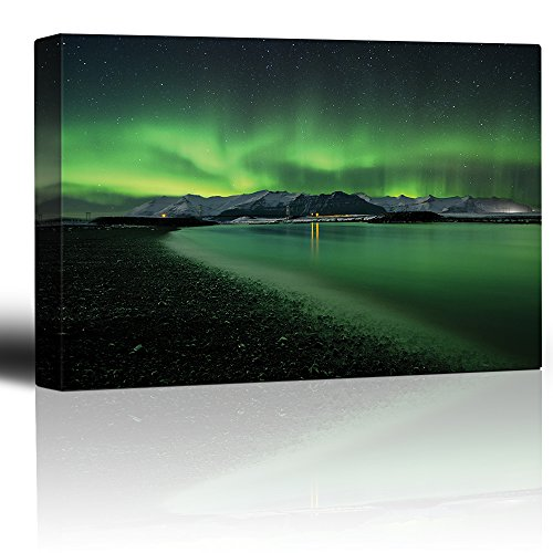 Green Northern Lights Above Snowed in Mountains and Being Reflected on a Lake