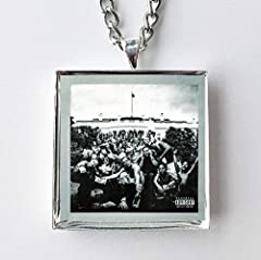 """This is a necklace featuring album art of the """"To Pimp A Butterfly"""" record by Kendrick Lamar in a silvertone metal setting with glass. The album cover pendant is 1"""" and on a 20"""" long silvertone neck chain. The necklace is individually handcra..."""