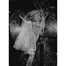 Vintage photo of Dressed beauty at the opera costume sitting in a globe suspended from the ceiling