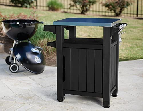 51elCKHHKeL. AC Keter Unity Portable Outdoor Table and Storage Cabinet with Hooks for Grill Accessories-Stainless Steel Top for Patio Kitchen Island or Bar Cart, Dark Grey    This plastic outdoor kitchen storage table with wheels combines two storage solutions in one, providing a stainless steel top for serving drinks or condiments and a cupboard for storing extra supplies. It works perfectly for a family barbecue or any friendly gatherings on the deck, giving you extra serving and storage space for plates, water bottles and more. Place snacks on the durable surface for friends to grab any time, and keep cloth napkins or grilling utensils hung easily within reach on the additional hooks.