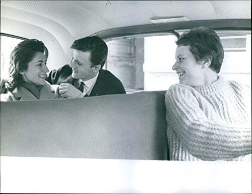 - Vintage photo of A man and a woman smiles at each other while inside on the backseat of the car and the driver smilingly looks at them, 1963.