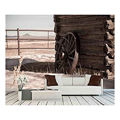 A Wagon Wheel Resting Against an Old Cabin with Mountains in The Distance - Removable Wall Mural | Self-Adhesive Large Wallpaper - 66x96 inches