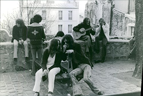Vintage photo of 1973One man is playing guitar sitting on a wall and one man is sitting beside him. On that wall there are some more people talking to each other. In front of that wall there is an arrangement of sitting and some people are sitting there and talking to each other.