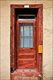 Photograph of very colorful red American Southwest door on adobe wall with yellow mailbox.