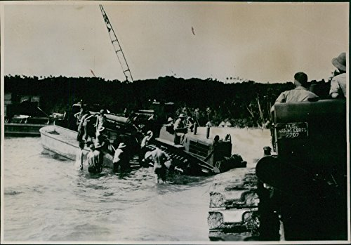 Vintage photo of A tractor drags this big field gun from the barge to shore, 1942. ()