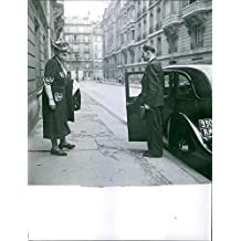Vintage photo of Eug233;nie Berthe Hardon wife of Marshal P233;tain going inside the car, man assisting her, 1962.