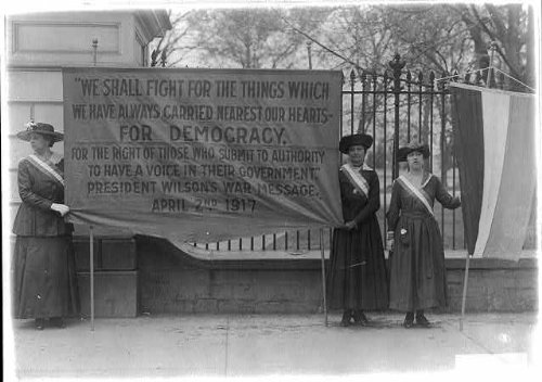 Holding Banner (Photo: Three suffragettes holding a banner in front of White House,D.C.,c1917,Flag)