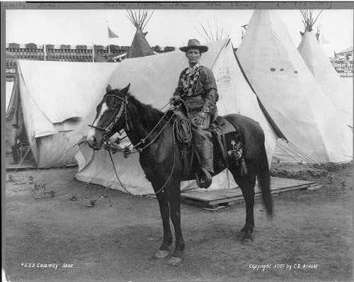 Calamity Jane Costume (1901 Photo Calamity Jane Photographs shows Martha Jane Burke, popularly known as Calamity Jane, on horseback, wearing an elaborate Western costume, in front of tipis and tents at the Pan-American Expo)