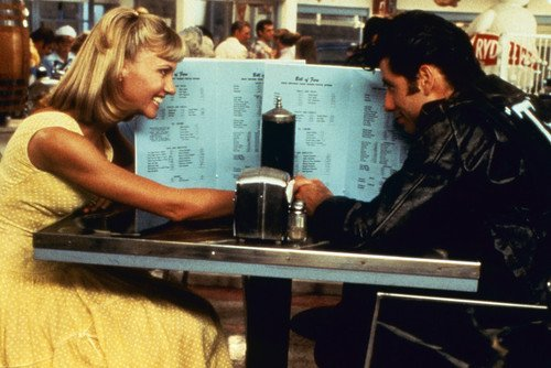John Travolta and Olivia Newton-John in Grease seated in diner hiding behind menus 24x36 Poster from Silverscreen